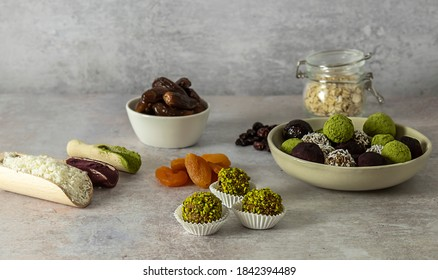 Healthy energy confection balls without artificial sugar, no baking, vegan candy snack made from oats and dry dates, cranberries, apricots with matcha, coconut flakes, and ube powder.