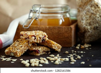 Healthy energy granola bars with dried cranberries on a dark wooden background close-up. Healthy snack of oats, nuts and honey. Vegetarianism and healthy food concept. - Image