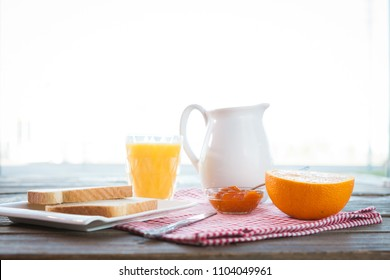 Healthy english breakfast with toasts, orange juice and jam on the table close up