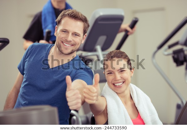 Healthy enthusiastic young couple in a gym giving a thumbs up of approval while smiling at the camera in a health and fitness concept