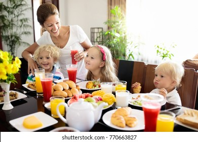 Healthy family breakfast at home. Mother and kids eating tropical fruit, toast bread, cheese and sausage. Children drink fresh pressed juice on sunny morning. Mom, boy, girl and baby eat breakfast.