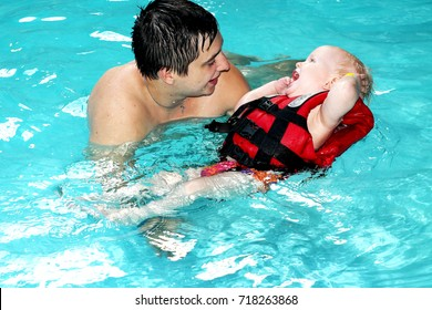 healthy family father teaching baby swimming pool. the little blond boy learns to swim in the life jacket. Dad carefully and fun teaches the child to swim