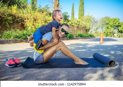 Healthy family life, cute cheerful baby boy plays piggy back and helps her to do stretching, beautiful woman with her little son doing sport excercises outdoors