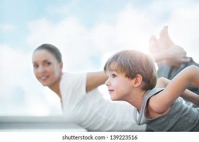 Healthy family - mother and son doing exercises against blue sky