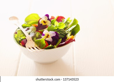 Healthy farm fresh herb salad with leafy greens and nasturtium flowers served in a white bowl with a fork on a wooden white table