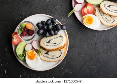 A healthy farmer family breakfast snack. Slices of cereal bread with nuts, poppy rolls, halves of boiled egg, cucumber, radish, fresh juicy vegetables and berries. Top View