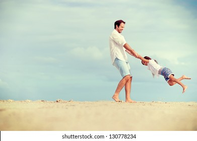 Healthy father and daughter playing together at the beach carefree happy fun smiling lifestyle