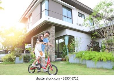 Healthy father and daughter playing together outside their new house. Home fun  lifestyle, family concept.