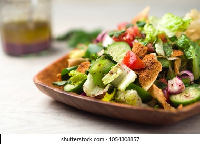 Healthy fattoush salad closeup. The key ingredient in this middle eastern dish is the toasted pita bread which is mixed with healthy vegetables, herbs and a dressing made with lemon and sumac.
