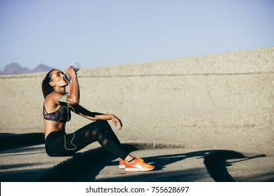 Healthy female sitting outdoors and drinking water after exercising session. Fitness woman taking a break after workout.