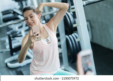 healthy fit and firm woman relax with selfie in gym and feel good with her body