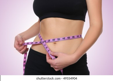 A healthy, fit girl measuring her waist after fitness exercise