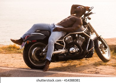 Healthy, fit and muscular black african american man on a motorcycle near the sea in the sunset