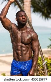 Healthy, fit and muscular black african american man on a beach takes shower