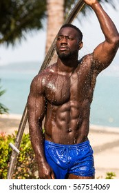 Healthy, fit and muscular black african american man on a beach taking shower