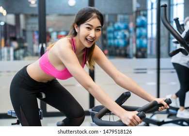 Healthy fit smiling woman training at gym on exercise static bike for good health