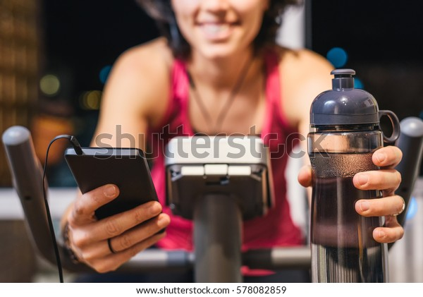 Healthy fit smiling woman training at home on exercise static bike during workout holding phone and bottle of water while listening music with earphones for motivation. Female health weekly habits app