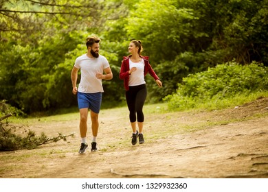 Healthy fit and sportive couple running in nature at summer day