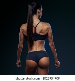Healthy fit strong young woman in sportswear standing with her back looking over her shoulder Copy space Clipping path Rear view Muscular power female back, booty, buttocks
