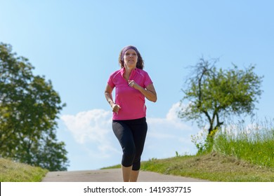 Healthy fit woman enjoying a jog in spring sunshine running along a country road against a blue cloudy sky in an outdoors fitness concept