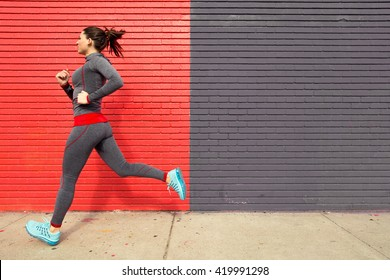 Healthy fit woman exercising with a run jog in the city sidewalk confident and powerful