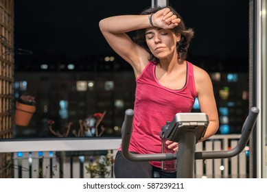 Healthy fit woman training at home on exercise static bike during workout feeling exhausted and dizzy rising forearm to her forehead holding a bottle of water. Active female health weekly habits.