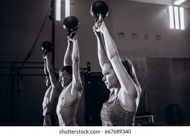 Healthy fit young athletes doing exercises with kettlebells at gym, men and women during weight lifting workout