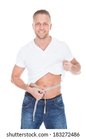 7c5588cb10c Healthy fit young man lifting up his white t-shirt and measuring his waist  with