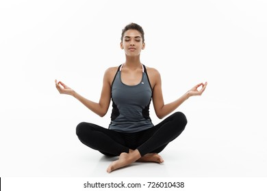 Healthy and Fitness concept - Beautiful American African lady in fitness cloth doing yoga and meditation. Isolated on white background.