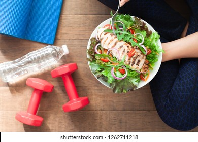 Healthy and fitness food. Chicken salad dish with fitness equipments