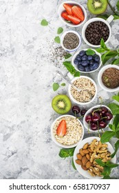 Healthy fitness food from fresh fruits, berries, greens, super food: kinoa, chia seeds, flax seed, strawberry, blueberry, kiwi, cherry, almonds, walnuts, mint, oatmeall flakes on a light background.