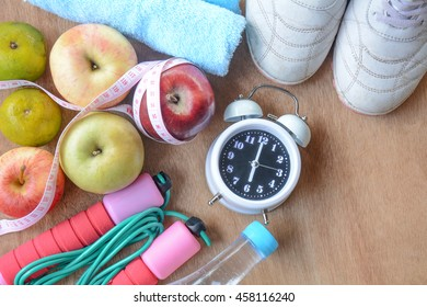 Healthy fitness and fruit concept with Exercise Equipment and fruit lose weight on wooden background.
