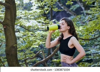 Healthy fitness girl drinking water from green bottle in forest