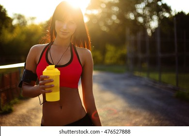 healthy fitness girl with protein shake. sport and work out girl in sunny day