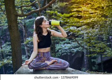 Healthy fitness girl sitting in lotus pose and drinking water from green bottle in forest