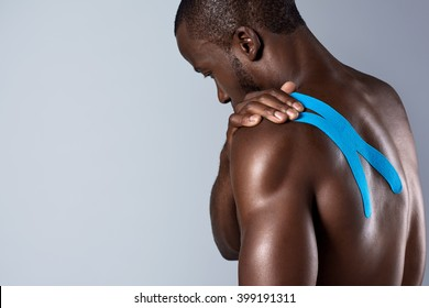 Healthy fitness man with taped shoulder muscle, hurt painful during exercise