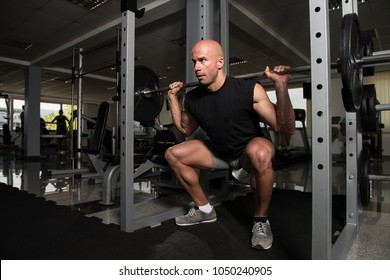 Healthy Fitness Man Working Out Legs With Barbell In A Gym - Front Squat Exercise