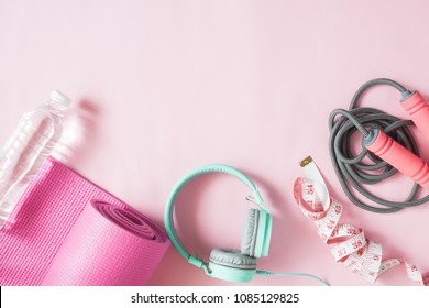 Healthy flat lay with sport and fitness equipments and mint color headphones on pink color background