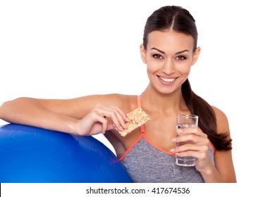 Healthy food after-workout is the way to success! Cropped shot of attractive sporty woman sitting next to her fitness ball and holding a protein bar with glass of water.
