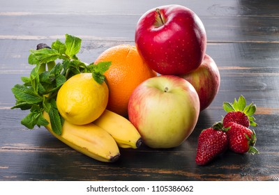 healthy food apples, citrus fruits, berries. on dark background diet products. fresh fruit lie on a wooden table.