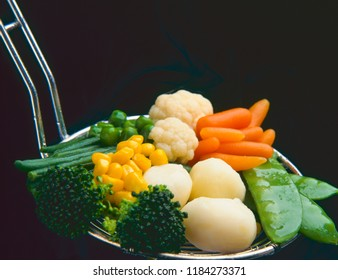 Healthy food. Assorted vegetables cooking in skimmer.