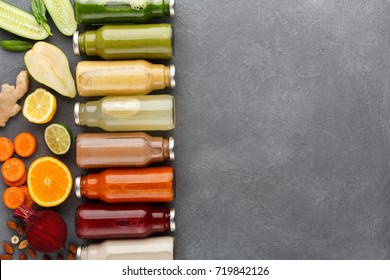Healthy food. Assortment of fruit and vegetables detox smoothies in glass bottles with ingredients on gray background, copy space, top view