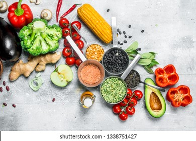 Healthy food. Assortment of organic vegetables and fruits with legumes. On a rustic background.