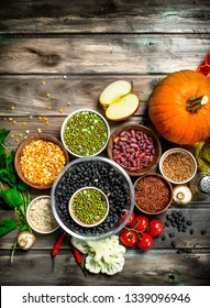 Healthy food. Healthy assortment of vegetables and fruits with legumes. On a wooden background.