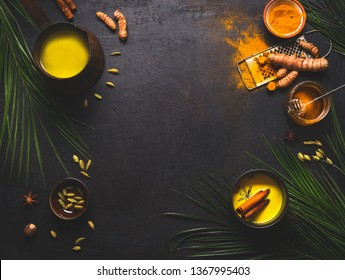 Healthy food background with detox turmeric milk preparation and ingredients on dark background, top view. Copy space. Healthy hot beverages concept. Natural immune boosting