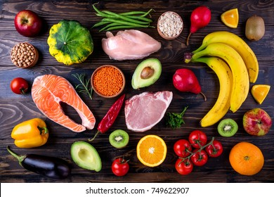 Healthy food background. Fish, meat, grains, vegetables, fruits on wooden table. Healthy food, diet and healthy life concept. Top view, flat lay. Copy space