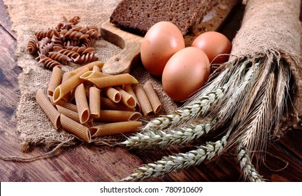 Healthy food background. Free GMO ears of cereals, pasta, bread, eggs on an old wooden table.