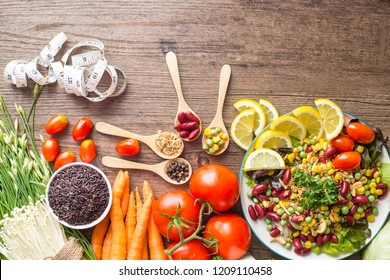 Healthy food background ,fruits and vegetables with salad bowl and measuring tape  on wooden table.