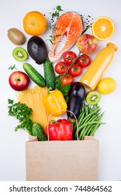 Healthy food background. Healthy food in full paper bag of different products fish, vegetables and fruits on white background. Top view