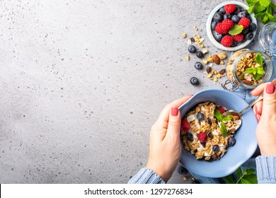 Healthy food background with homemade oatmeal granola or muesli with yogurt and fresh berries for healthy morning breakfast, top view, copy space.